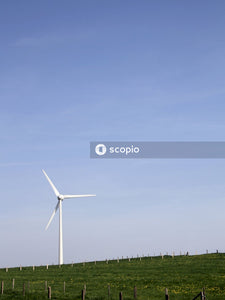 White wind turbine on green grass field under blue sky