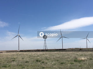 Wind turbines on green grass field under blue sky