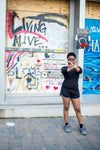 Woman in black t-shirt and black shorts standing beside wall with graffiti