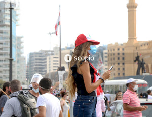 Woman in black tank top and blue denim jeans holding smartphone