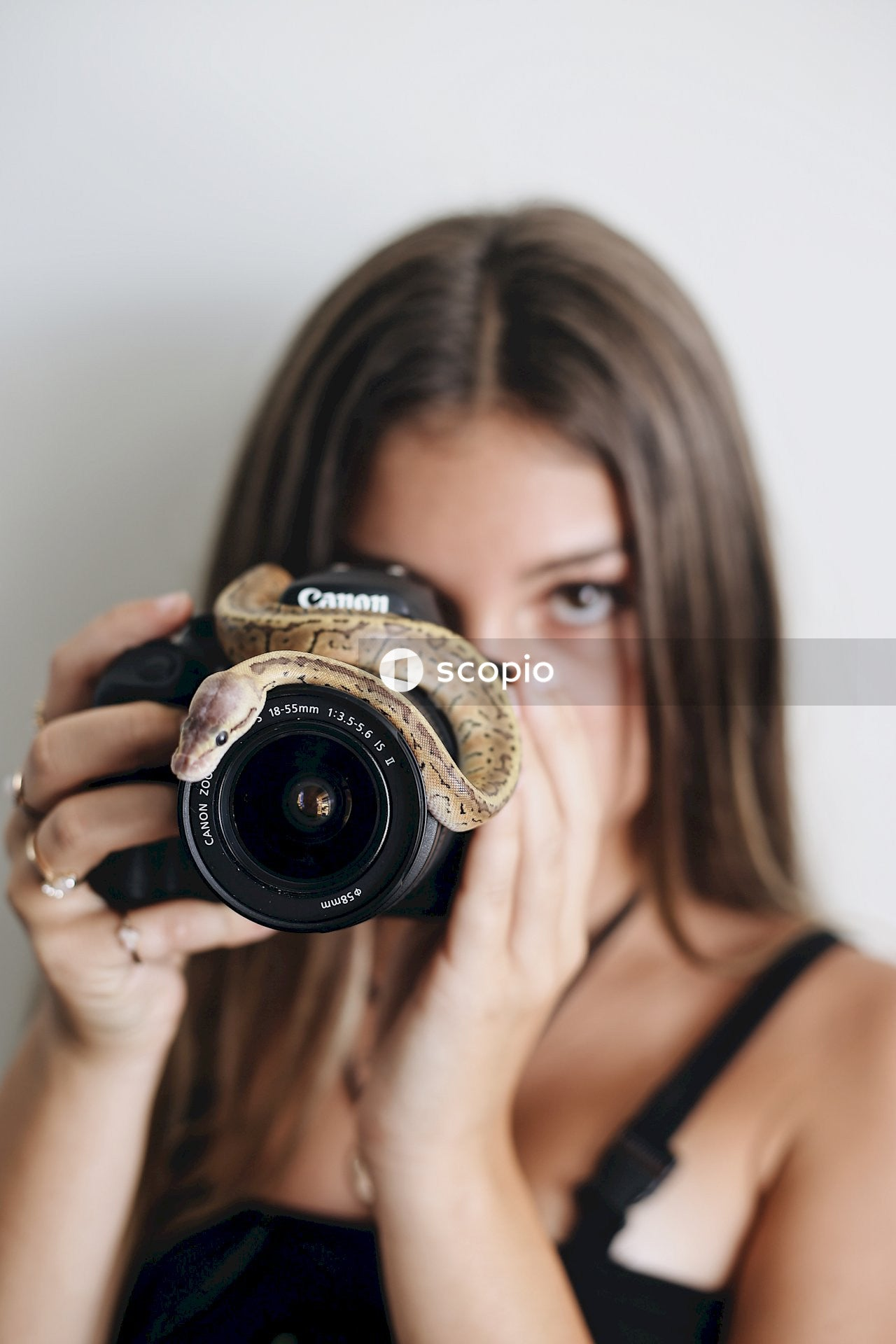 Woman in black tank top holding black nikon dslr camera