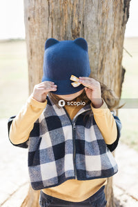 Woman in blue and white checkered long sleeve shirt covering her face with blue knit cap