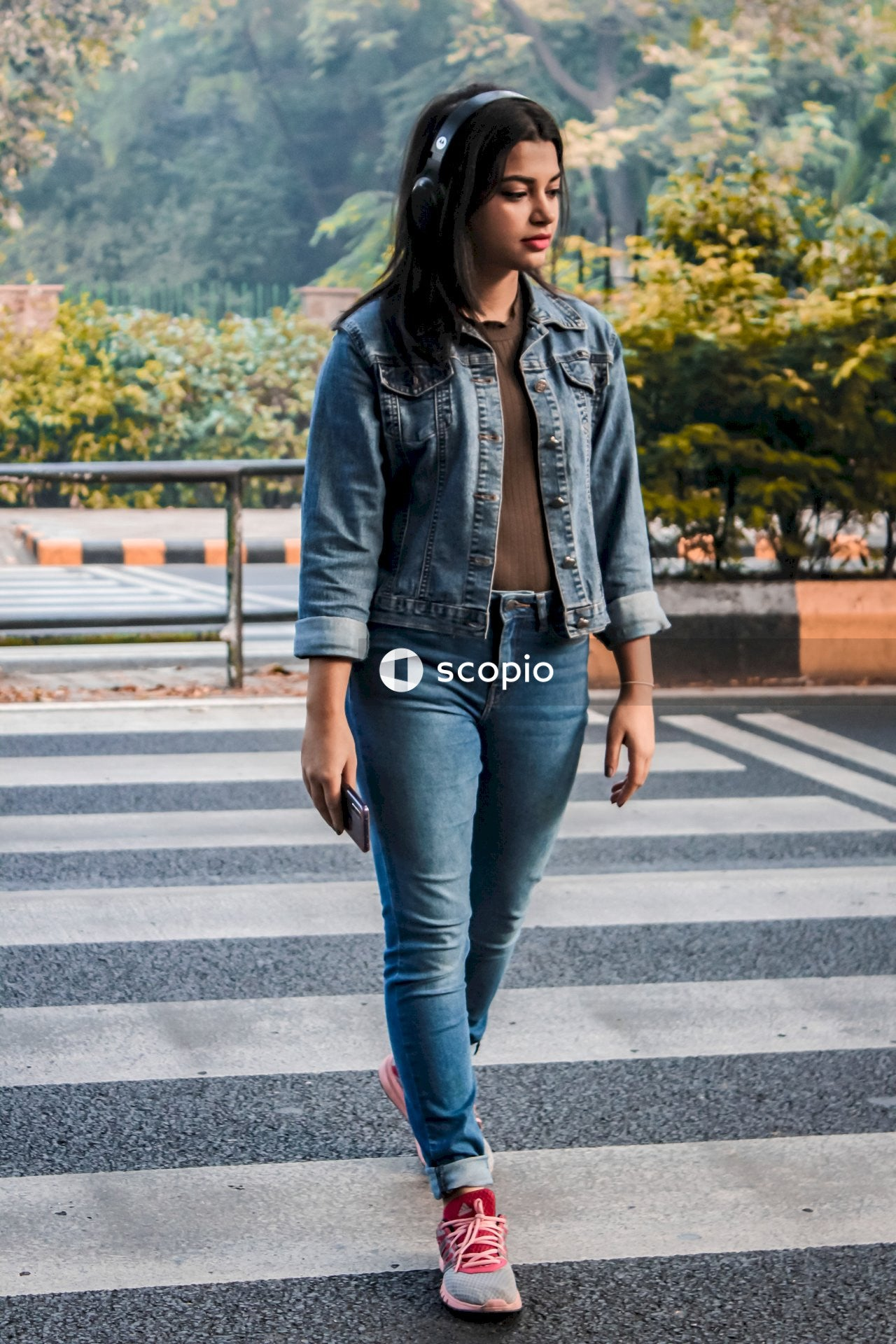 Woman in blue denim jacket and blue denim jeans standing on pedestrian lane