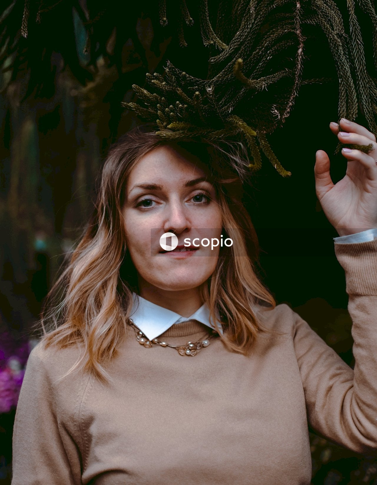 Woman in brown long sleeve shirt holding green plant