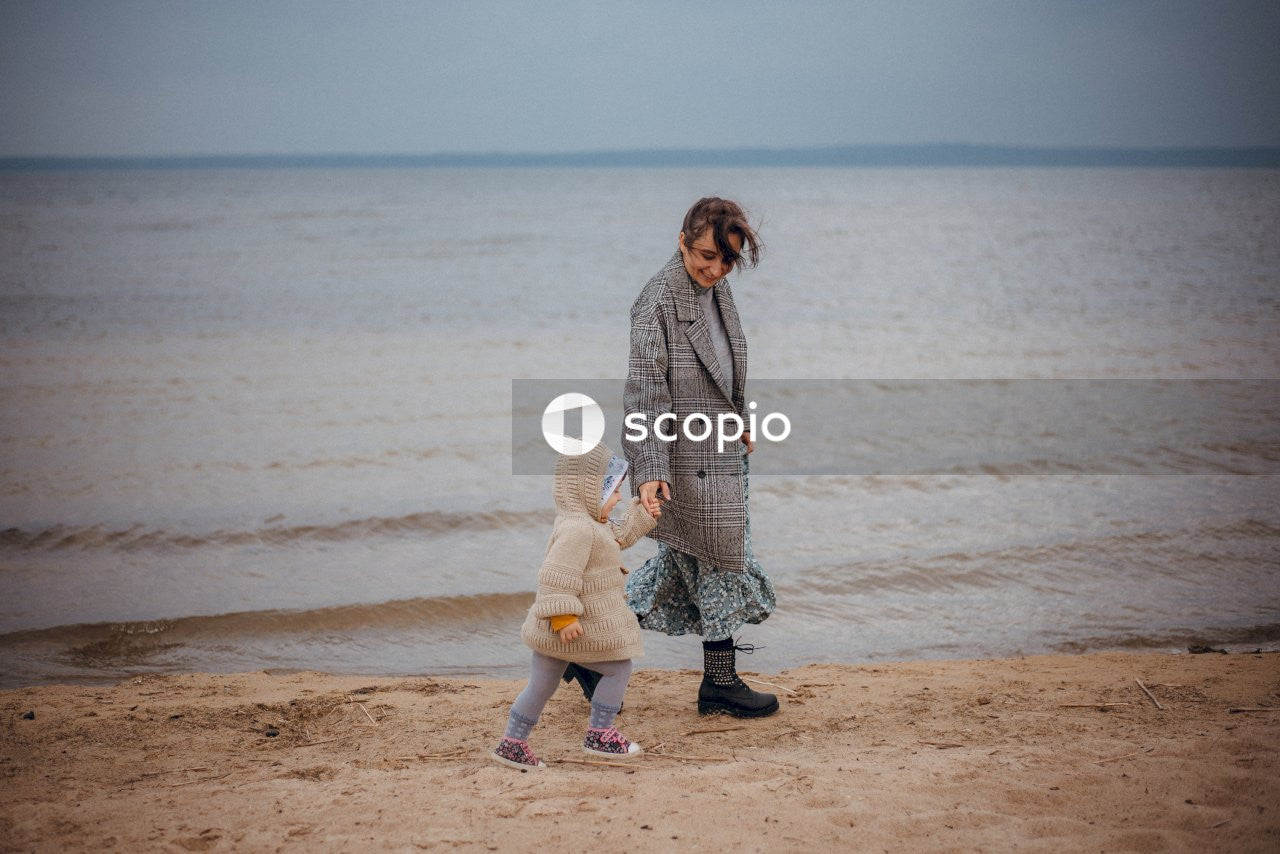 Woman in gray coat holding baby in white onesie on beach