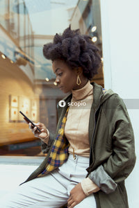 Woman in green jacket holding smartphone