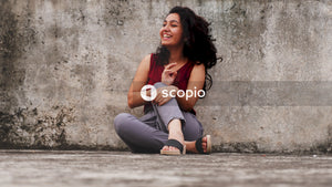 Woman in pink tank top and gray pants sitting on concrete floor