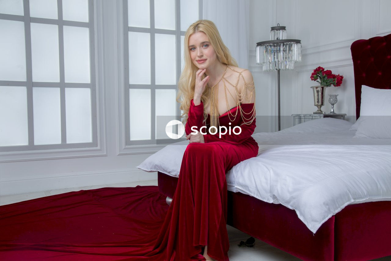 Woman in red dress sitting on bed