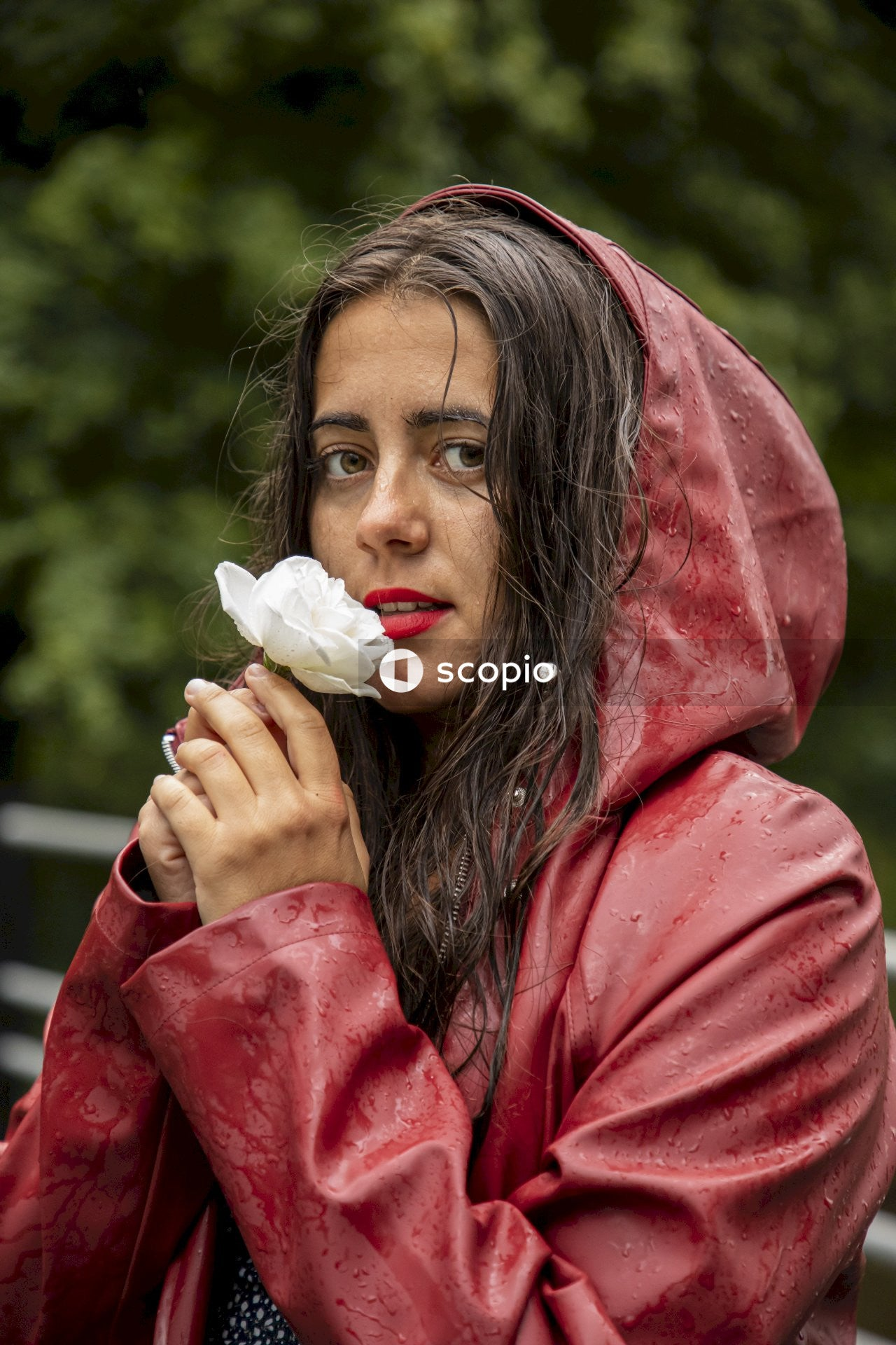 Woman in red hoodie holding white flower