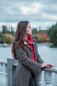 Woman in red scarf and gray sweater sitting on white wooden bench