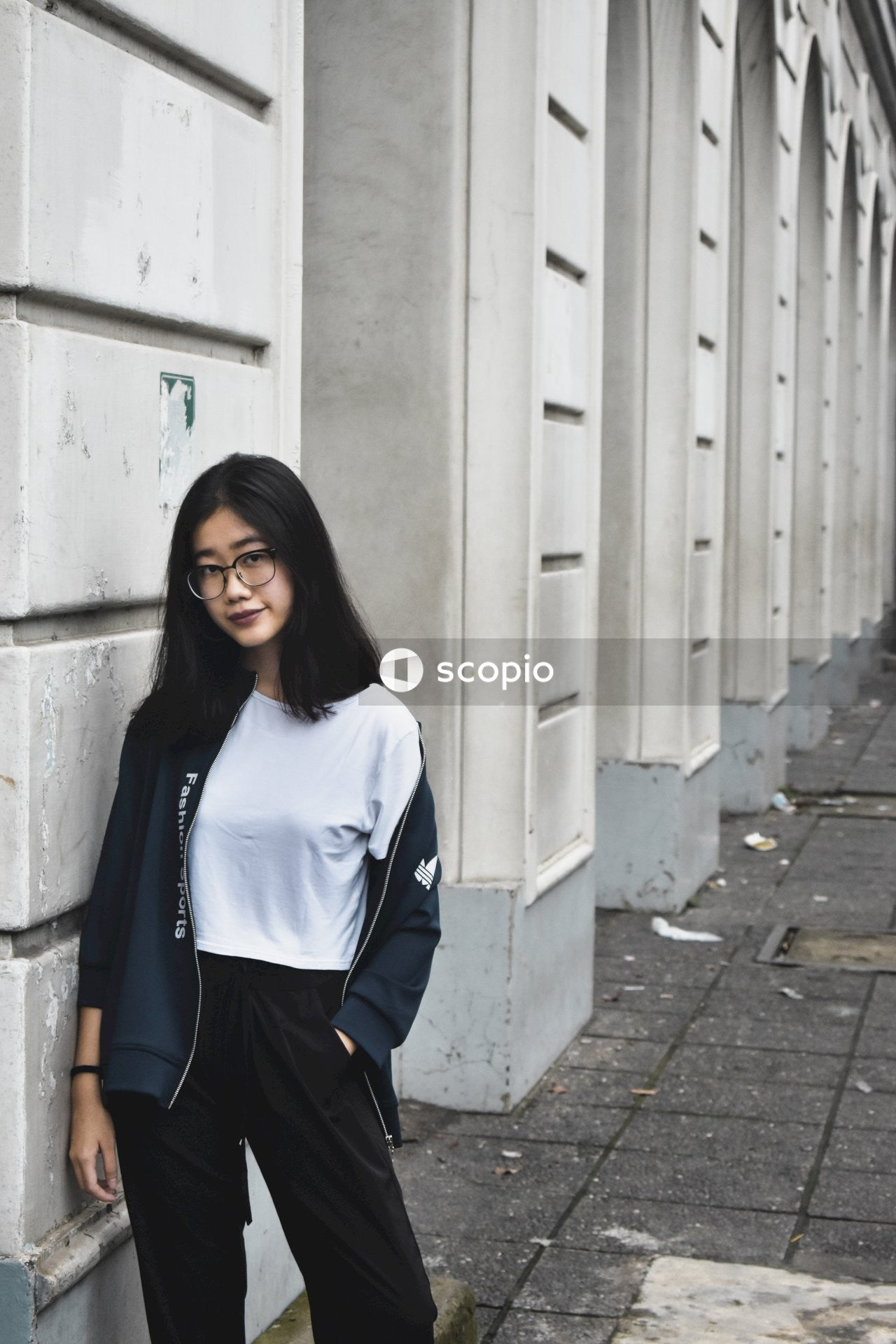 Woman in white and blue long sleeve shirt and black skirt standing beside white concrete wall