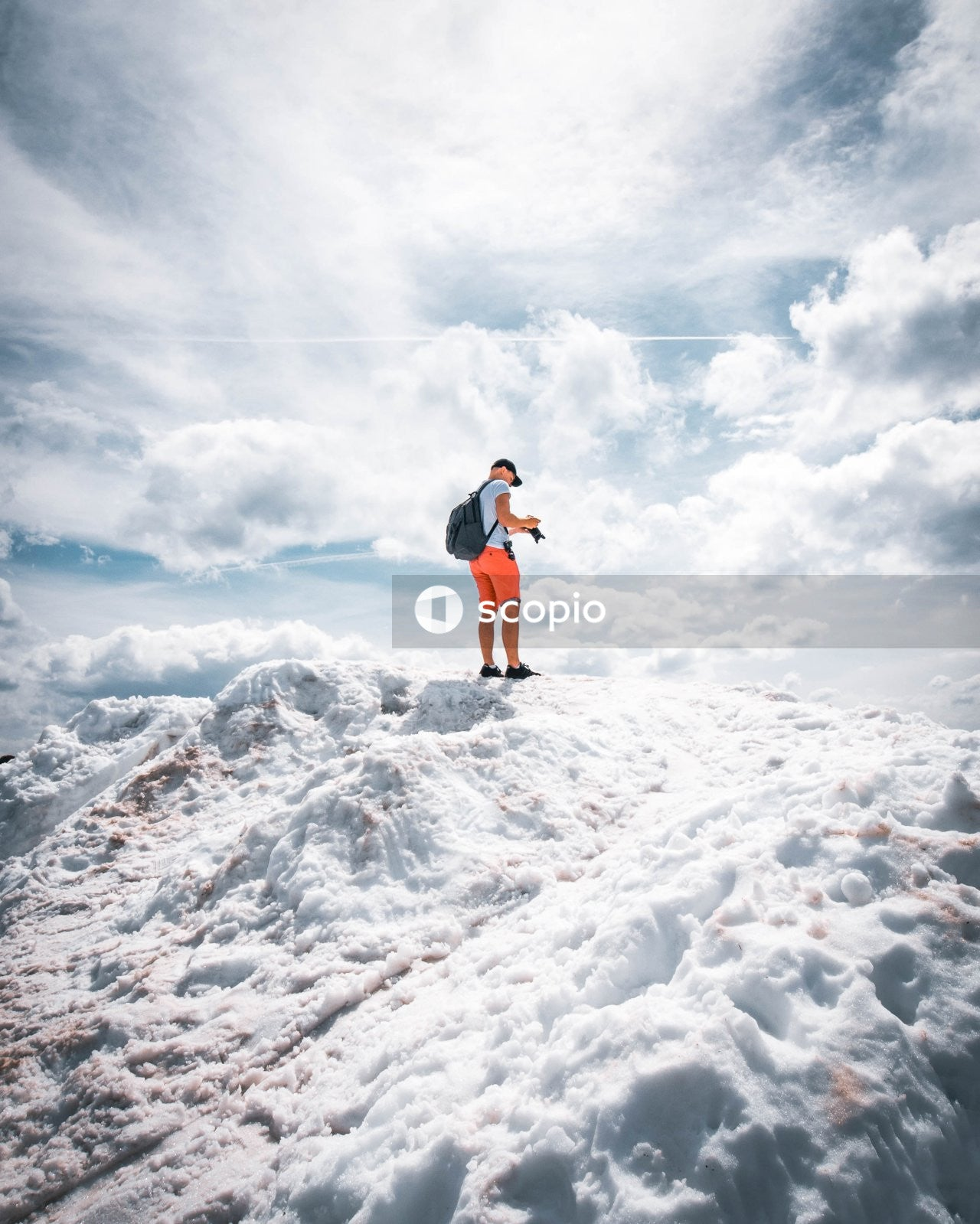Woman in white shirt and blue denim shorts standing on white snow covered ground under white