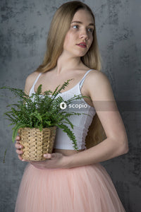 Woman in white spaghetti strap top holding green plant
