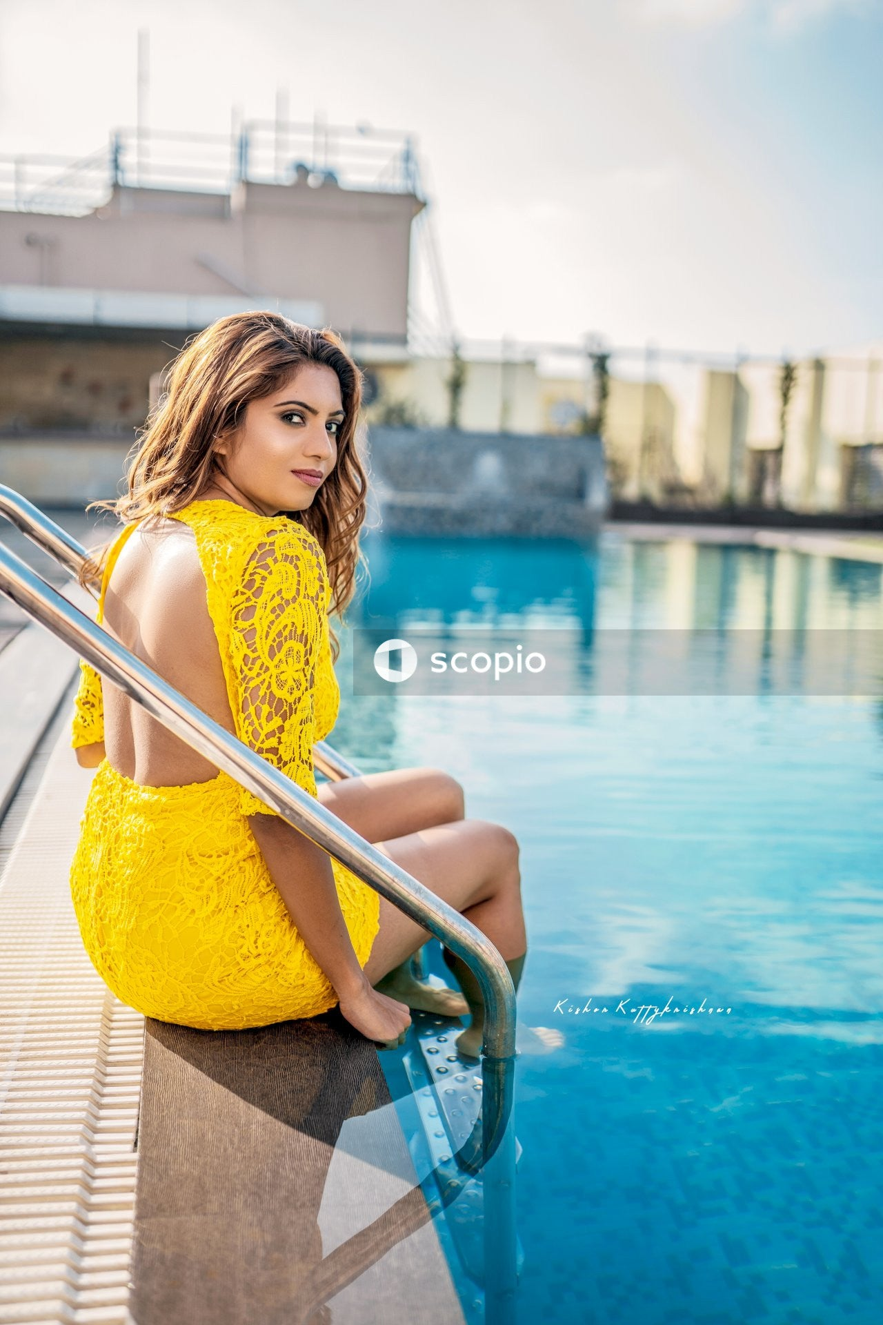 Woman in yellow dress sitting on pool ladder