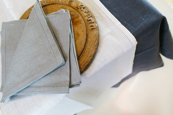 From above, Modern Classic Tablecloths with hem stitch detail available from Pekho, in white and charcoal linen.