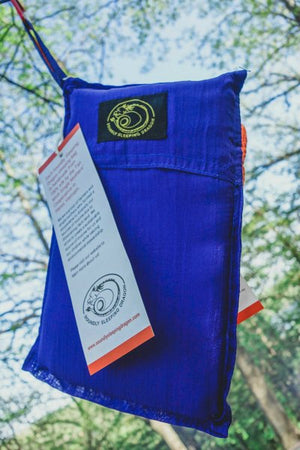 blue sleeping bag hanging from a tree