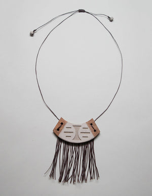 Yomo Studio crescent necklace. Materials include: concrete, walnut wood, and wax string.