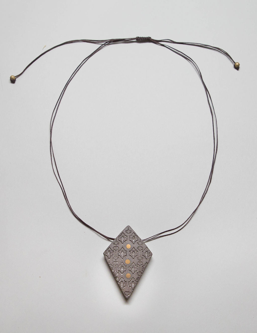 Yomo Studio rhombus dots necklace. Materials include: concrete, brass, metal beads, and wax string.