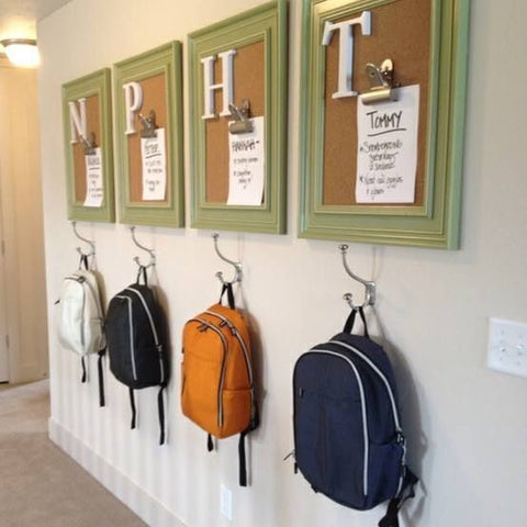 Backpacks hanging on wall hooks with bulletin boards above them.