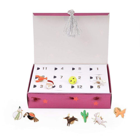 Advent calendar with enamel pins inside in shapes like cactus, pizza, reindeer, and butterfly.