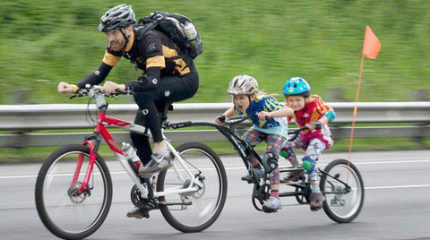 Dad biking riding with children