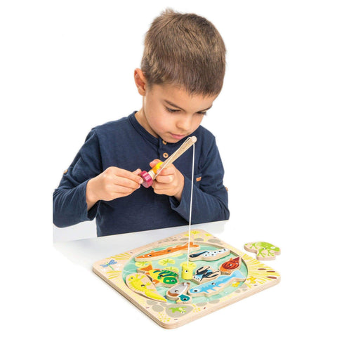 Boy playing with magnetic fishing pole toy that fishes for wooden fish.