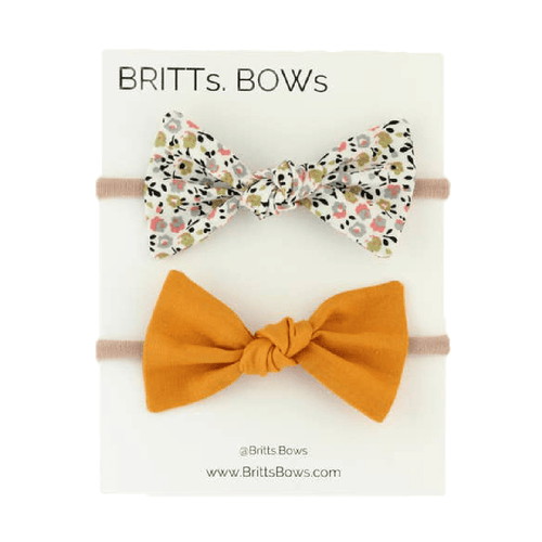 Two baby bow headbands, with a white and floral bow and mustard yellow bow.