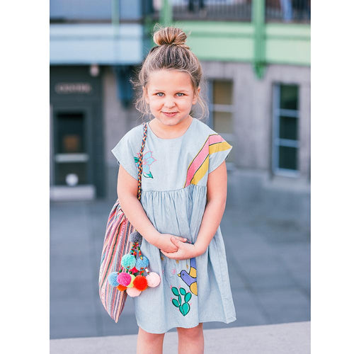 Girl in blue dress with pink pom pom bag
