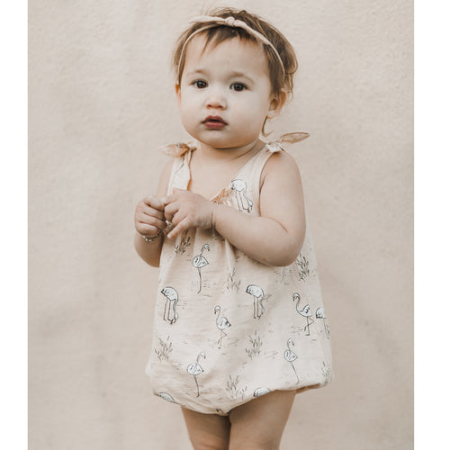 Light pink bubble romper with tie shoulders and flamingo print for baby girl