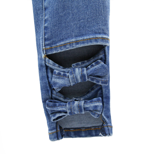 Close up of girls bow ankle skinny jeans