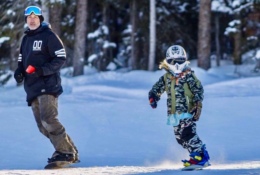 Father and child snowboarding together