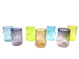 seven drinking glasses in bright colours; blue, purple, lime green and brown
