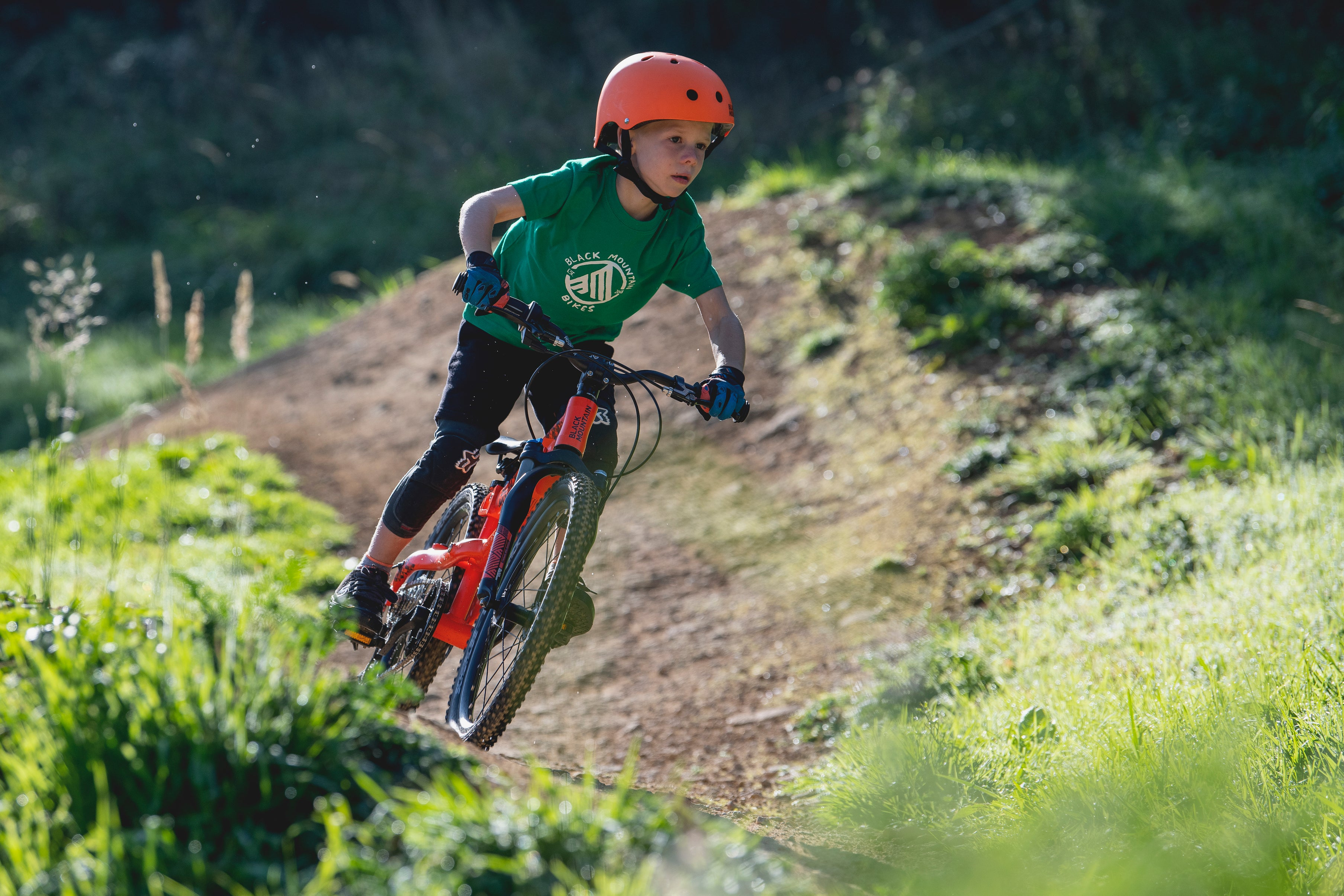 "Boy riding 20"" mountain bike on trail"