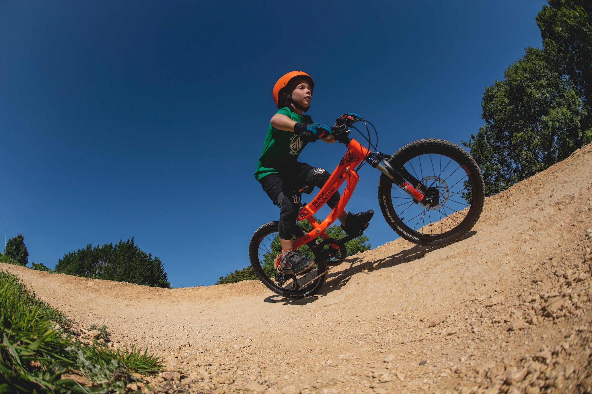 Child riding mountain bike on berm