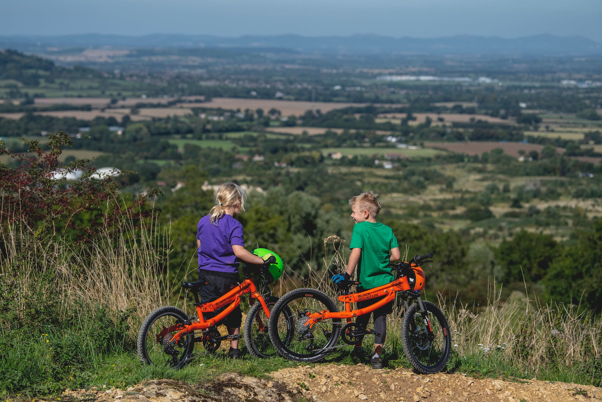 Boy and girl on hill with mountain bikes