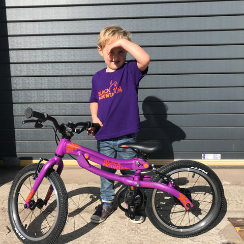 Boy standing with lightweight kids bike