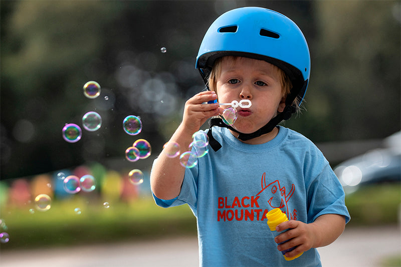 Young cyclist blowing bubbles