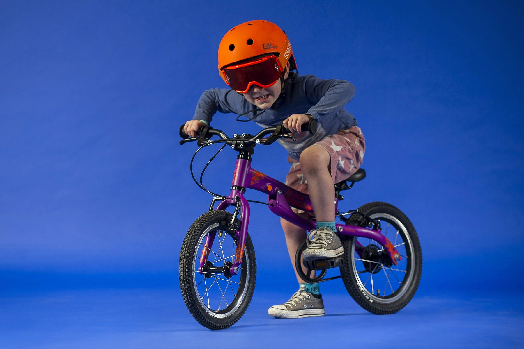 Young boy on bike in helmet and goggles