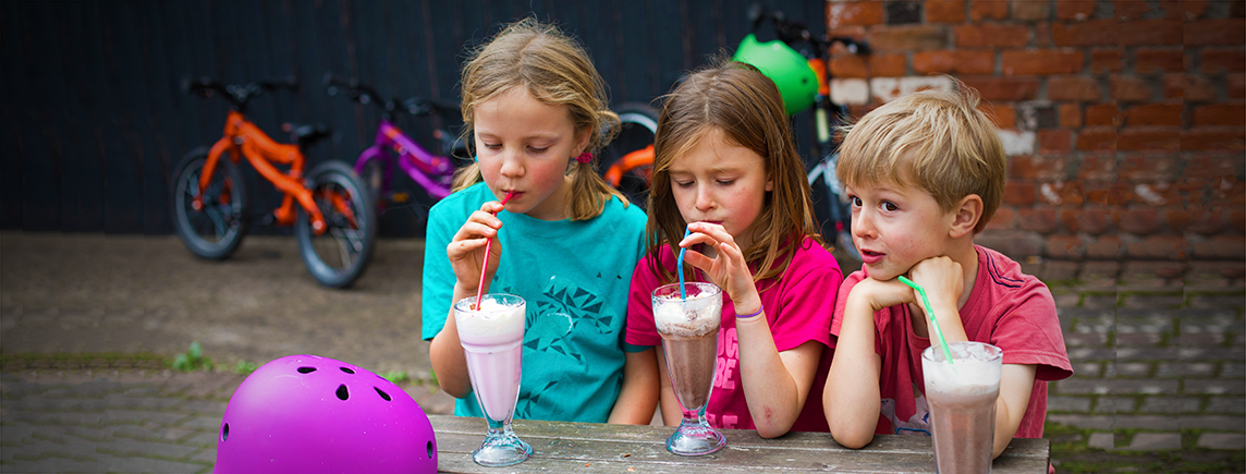 Kids drinking milkshake after bike ride