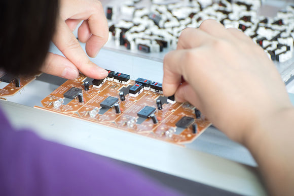 A factory workers assembles a piece of electronic equipment for a manufacturer