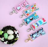 A Collection of Easter themed LippyClips on a pale pink background with a nest of eggs.