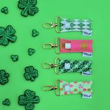 St. Patricks themed LippyClips on a green background with shamrock scatters.