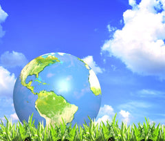 Earth resting on green grass with bright blue sky and white clouds in background.