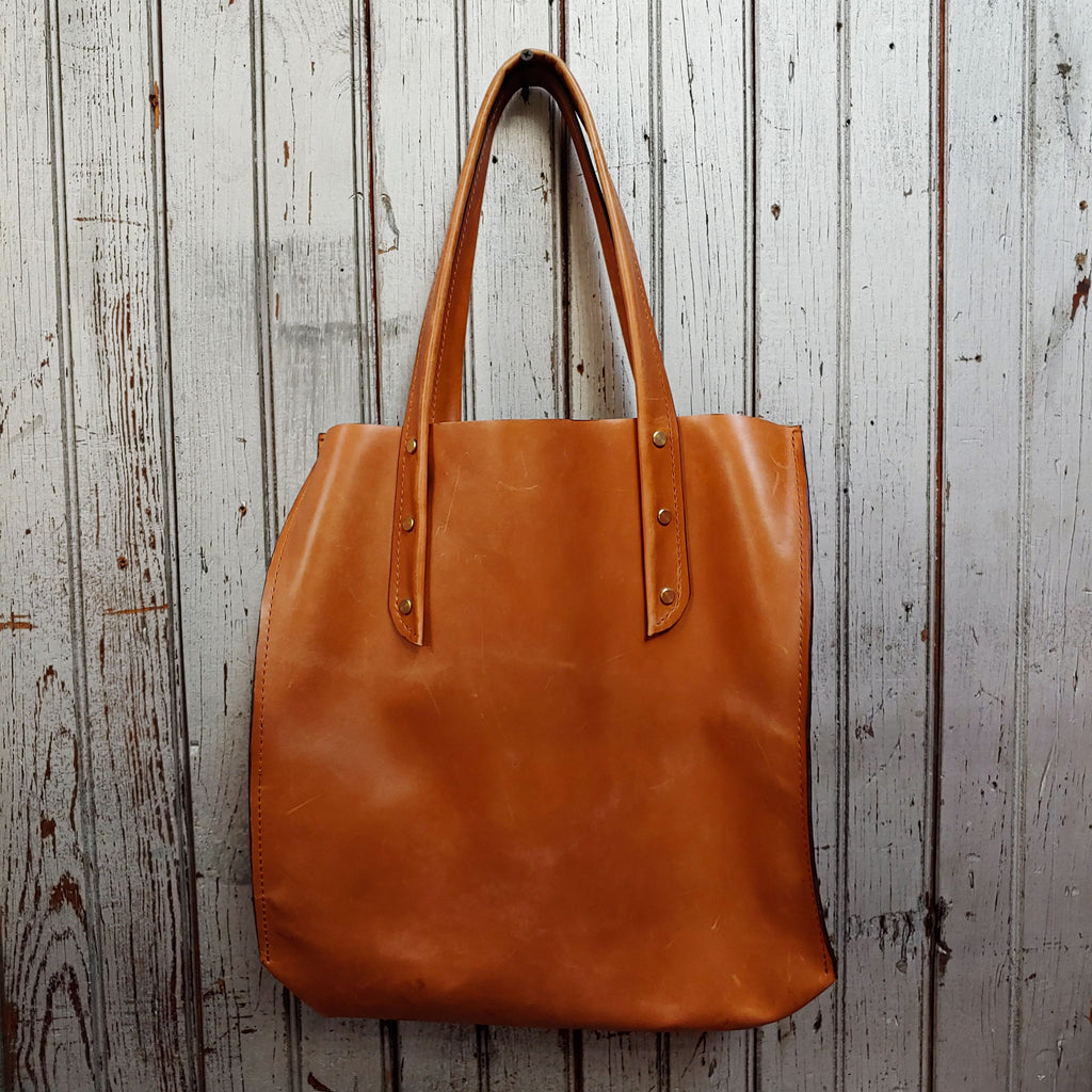 "Front facing view of ""large leather tote"" in camel against a wood paneled background."