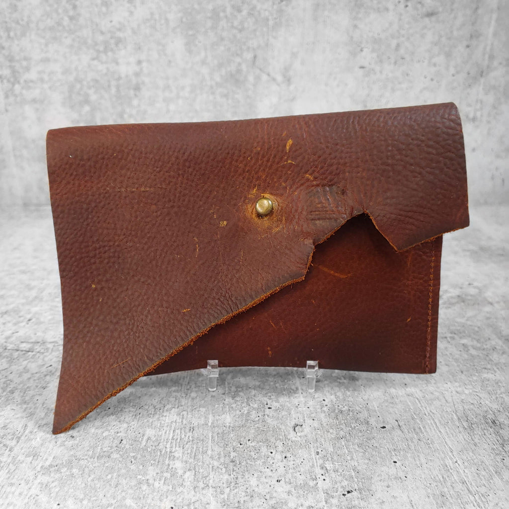 "Front facing view of ""asymmetric leather wallet with belt loops"" in hickory against a concrete background."