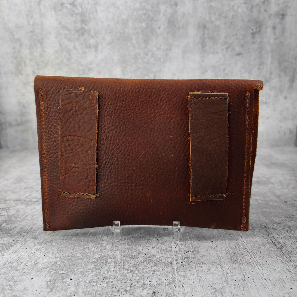 "Back view of ""asymmetric leather wallet with belt loops"" in hickory against a concrete background."