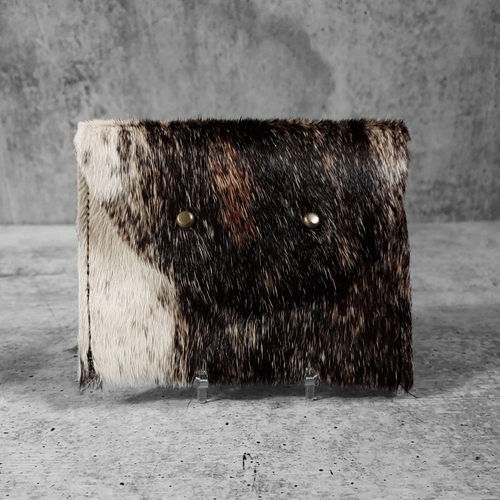 "Front facing view of ""large raw hide wallet"" in natural against a concrete background."