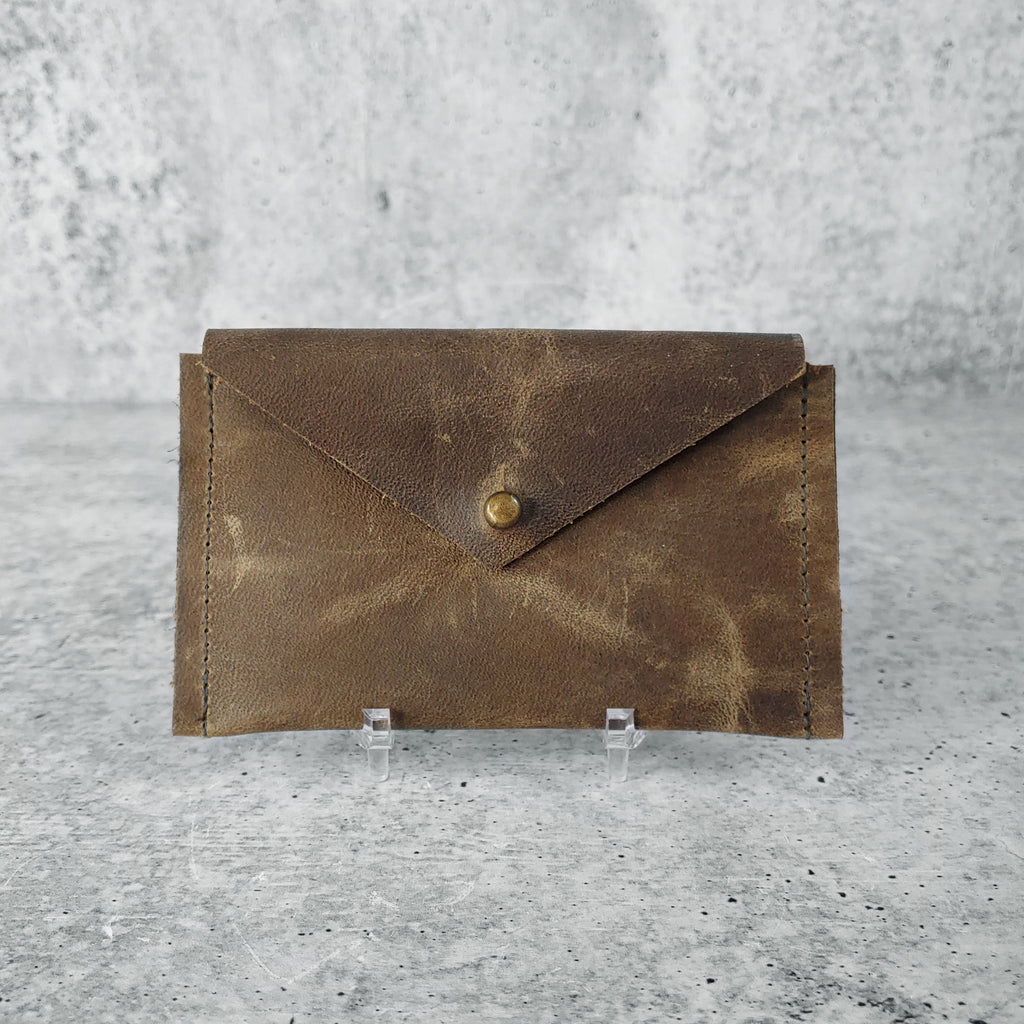 "Front facing view of ""leather card holder"" in ash brown against a concrete background."