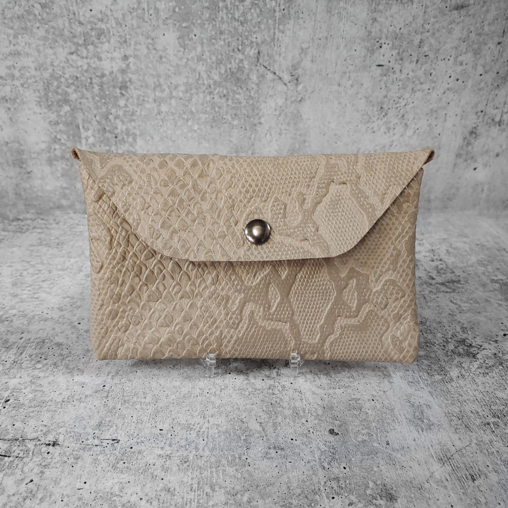 "Front facing view of ""leather clutch trapezoid"" in dovetail against a concrete background."