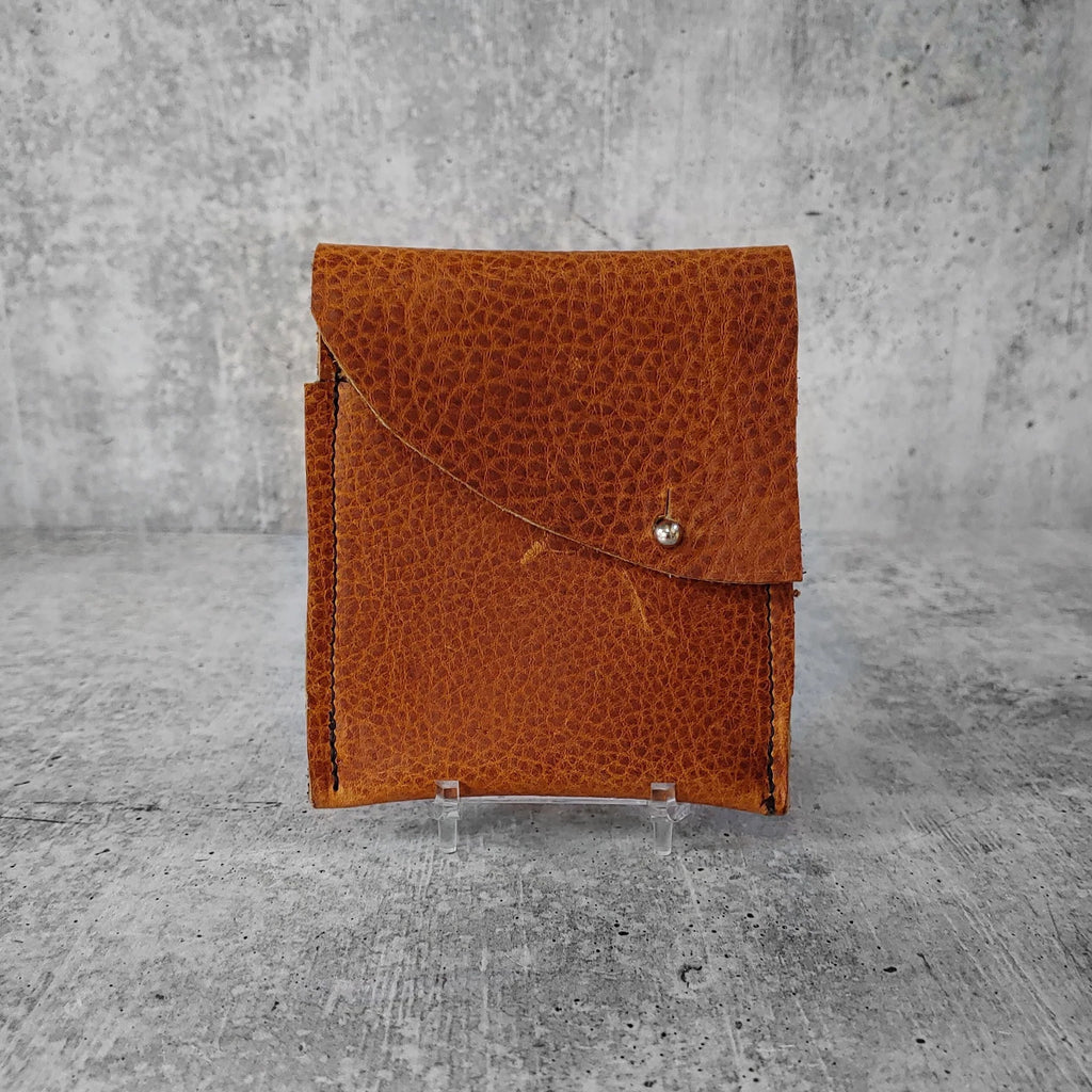 "Front facing view of ""leather wallet midi right"" in pecan brown against a concrete background."